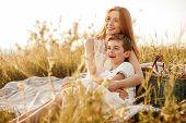 Optimistic Teenager Hugging Excited Little Boy While Sitting On Blanket Near Basket And Resting Toge poster