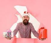 Santa Claus With Gifts Pokes Out Of Hole. Happy Man In Santa Hat With Presents Gifts Box Breaks Thro poster
