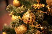 Christmas tree with gold bauble ornaments. Decorated Christmas tree closeup. Balls and illuminated g poster