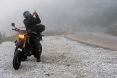 Rider Is Trying To Find Signal On His Mobile On A Foggy Day poster