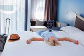 Woman Lying In The Bed Of A Hotel Room. Hotel Guest Relaxing On The Bed In Their Room. poster