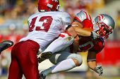 VIENNA, AUSTRIA - JUNE 5 RB Mario Nerad (#20 Austria) is tackled by DB Bobby Short (#43 Rose Hulman)