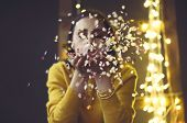 Happy Beautiful Brunette Girl Wearing Yellow Sweater Blowing On Confetti Isolated On Vintage Backgro poster