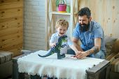 Adorable Little Child Plays With His Bearded Father With Plastic Dinosaurs. Son And Father Play In B poster