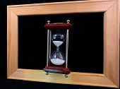 Hourglass In A Wooden Frame, On A Black Background. Glass Hourglass In A Frame For A Picture. Glass poster