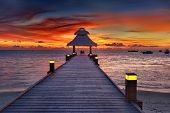 stock photo of dhoni  - Awesome vivid sunset over the jetty in the Indian ocean - JPG