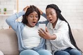 Unexpected Message. Two Shocked Black Girlfriends Looking At Smartphone Screen With Open Mouth, Sitt poster
