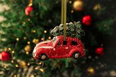 Small Red Car Bauble And Toys On A Christmas Tree. Christmas Composition. poster