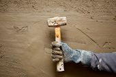 hammer man hand with gloves in grunge cement mortar background