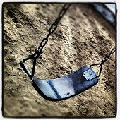 stock photo of swingset  - Empty swingset at the local park on a cold rainy day - JPG