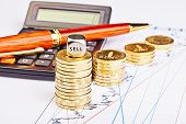 Downtrend Coins Stacks, Calculator, Pen And Dices Cube With The Word Sell On Financial Chart. Select