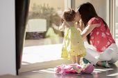 stock photo of baby doll  - Cute baby girl and her mother looking outside through a glass door - JPG