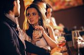 stock photo of flirt  - Young woman with a glass of wine talking to a man at the bar - JPG