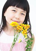 Happy little asian girl with yellow daisy