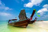 Tropical beach landscape. Traditional long tail boats at ocean gulf under blue sky. Thailand