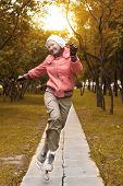 Yound Woman In Red Jacket Jumps And Have A Fun