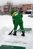 stock photo of shovel  - worker with a shovel clears snow in winter - JPG