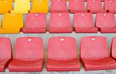 stock photo of grandstand  - Red and Orange Empty Seats in a Grandstand