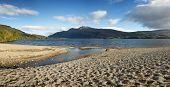 Panorama of a small shingle beach at the edge of Loch Lomond, Scotland.
