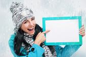 Smiling Girl Pointing At A Blank Board And Around Snowing
