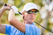 Athletic young man playing golf, golfer hitting fairway shot, swinging club