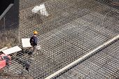 stock photo of reinforcing  - workers make metal reinforcement for the concrete foundation - JPG