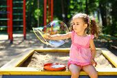 Little girl with tails sitting in a sandbox and blows the big bubbles