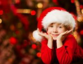 Christmas Child In Santa Hat Smiling Over Red Abstract Background