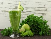 stock photo of vegan  - Glasses of green vegetable juice on bamboo mat on wooden background - JPG
