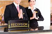 Chinese Asian reception team at luxury hotel front desk welcoming guests with typical gesture, a sig