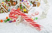 Three Red And White Candy Canes In Front Of Gingerbread Houses With Snow