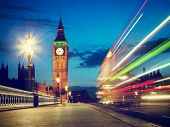 London, the UK. Red bus in motion and Big Ben, the Palace of Westminster at night. The icons of Engl