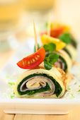 pic of crepes  - Crepe rolls as finger food filled with spinach and ham garnished with cherry tomato and watercress (Selective Focus Focus on the right upper part of the crepe roll and the right part of the cherry tomato on top)