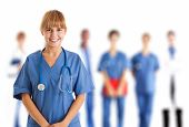 stock photo of nursing  - Young smiling nurse in front of her medical team - JPG
