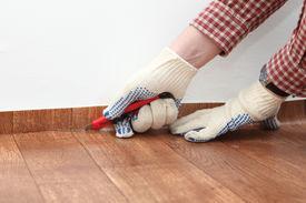 picture of linoleum  - Men cutting linoleum during the flooring installation  - JPG
