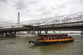 SINGAPORE - NOVEMBER 05, 2012: Tourist boat with tourists moving along the Singapore River. The Singapore River Cruise is one of the main tourist attractions of this exotic city.