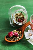 Assortment of herbs, tea in glass jars and cup of hot drink on wooden background