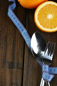 Cutlery tied with measuring tape and fruits on wooden background