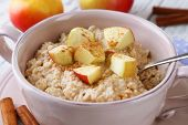 Tasty oatmeal with apples and cinnamon on wooden table