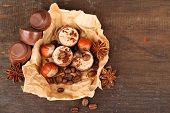 Tasty chocolate candies with coffee beans and nuts on wooden background