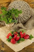 Strawberries with leaves on  on sackcloth napkin, on wooden background