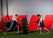 men flipping a tractor tire workout exercise at gym