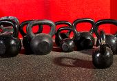 stock photo of kettlebell  - Kettlebells weights in a workout gym in red background - JPG