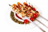 fresh turkey barbecue shish kebab served with tomatoes capers on platter isolated over white backgro