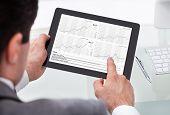 Businessman Analyzing Stock Market Status On Digital Tablet