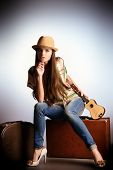 Attractive girl sitting on her old suitcases. Travel and tourism. Studio shot.