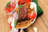 grilled meat : beef ( pork ) garnished with tomatoes salad in bowl , green chives , and tomatoes on