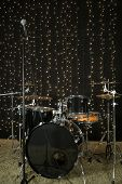 Drum set with microphones and cymbals in room with garland.