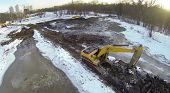 Excavators on dirt snow-covered ground reduced pond near the forest, view from unmanned quadrocopter.