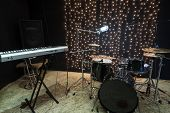 Studio room with keyboard, drum set and record equipment.